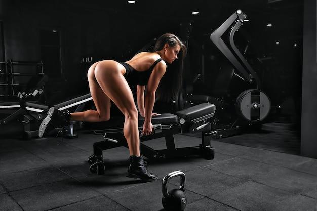 Фитнес-девушка с землекопами позирует на скамейке в тренажерном зале в яркой одежде с белым верхом и красными штанами фитнес-мотивацией.