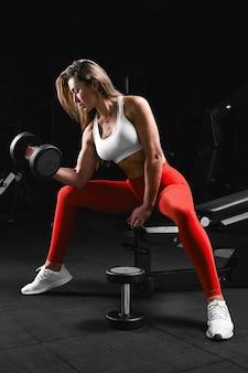 白いトップと赤いズボンのフィットネスの動機を持つ明るい服を着てジムのベンチでポーズをとる掘削機を持つフィットネスの女の子。