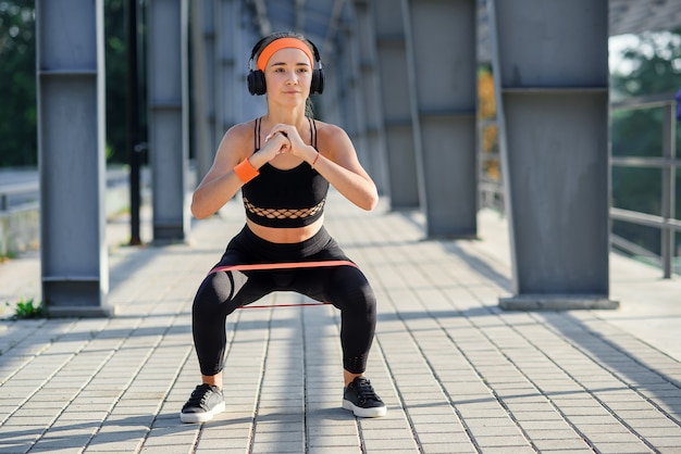Fitness girl with earphones which doing squat exercises with fabric booty band during her sport workout on special sportground