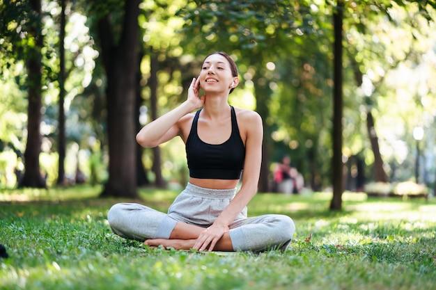 Ragazza di forma fisica con uno smartphone sulla natura gode di allenamento sportivo
