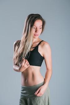 스포티 한 몸을 가진 피트 니스 소녀 회색 배경 피트 니스 웃는 모델에 스튜디오에서 포즈