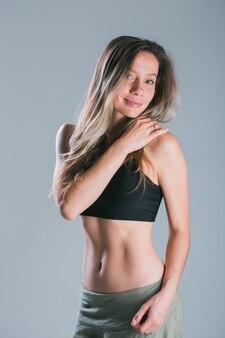 灰色の背景のフィットネス笑顔モデルのスタジオでポーズをとってスポーティな体を持つフィットネスの女の子