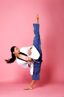 Fitness girl, woman can do concept. full length 12 years old athlete woman wear pastel sportswear and practice high kick karate, pink background, copy space