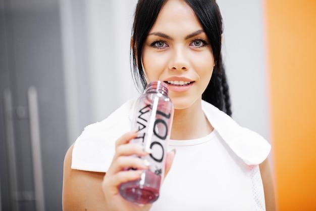 Fitness girl. young beautiful woman in sportswear drinking water