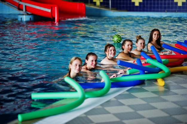 Fitness group of girls doing aerobical excercises in swimming pool at aqua park.