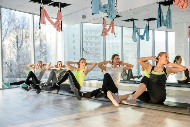 ジムで腹筋をトレーニングするフィットネスグループ