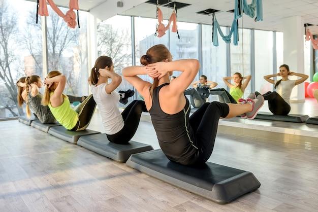 Фитнес-группа тренирует мышцы живота в тренажерном зале