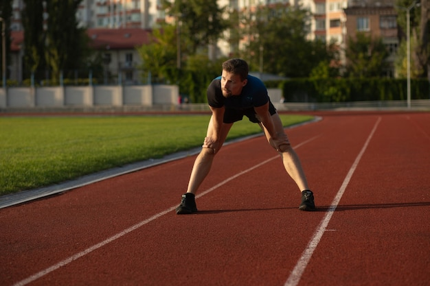 Fitness guy wears sport apparel preparing to jogging at the stadium. space for text