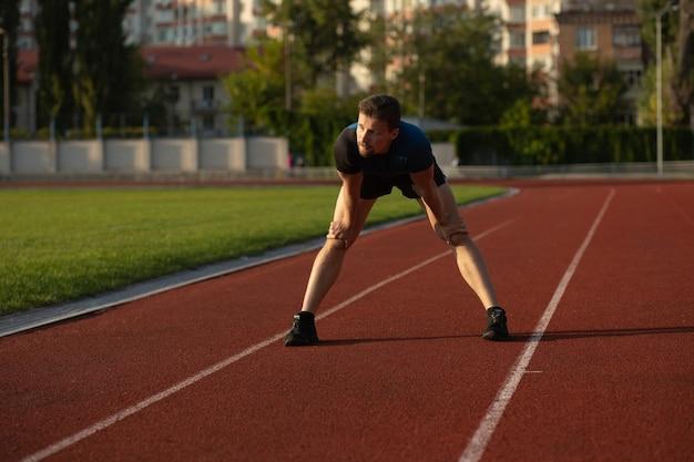 フィットネスの男は、スタジアムでジョギングする準備をしているスポーツウェアを着ています。テキスト用のスペース