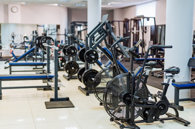 Fitness hall with sport bikes. metal bicycle trainers, equipment in gym.