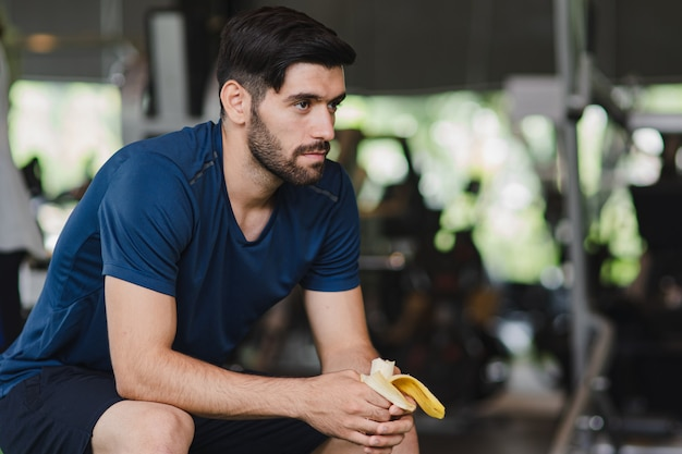Fitness handsome mid guy eating banana after workout in fitness studio