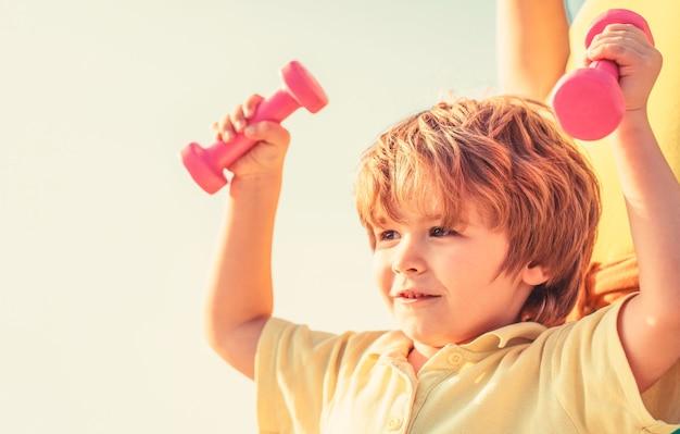 フィットネス、健康、エネルギー。健康的な生活様式。元気な男の子はダンベルでエクササイズをします。フィットネスの子供。ダンベルで運動する子供。小さな子供のためのスポーツ。