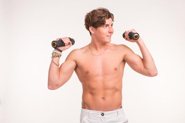 Фитнес, здоровый образ жизни и концепция людей - мускулистый красавец, делающий упражнения с легкими гантелями на белом фоне.