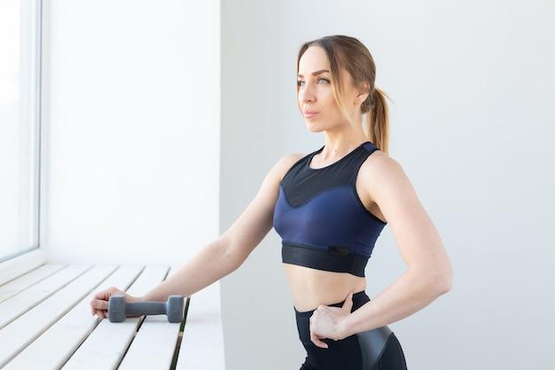 フィットネス、健康的なライフスタイルとスポーツのコンセプト-ダンベルを持つスポーティな女性の肖像画。