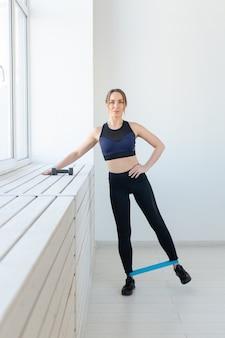 フィットネス、健康的なライフスタイル、スポーツのコンセプト-ゴムバンドで脚を振るストレッチをする若い女性。