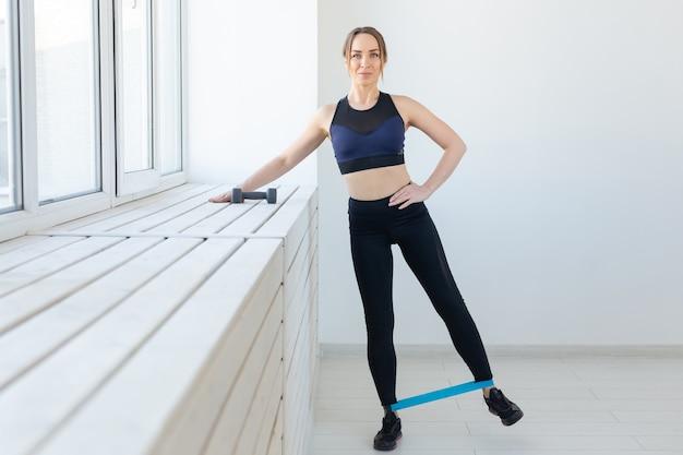 Фитнес, здоровый образ жизни и спортивная концепция - молодая женщина, растягивая, делая качели ноги с резинкой.