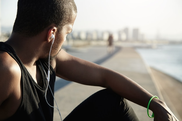 Fitness and healthy lifestyle concept. back shot of athlete having rest after workout in open air. dark skinned jogger in black a-shirt looking aside, listening to meditative sounds in earphones
