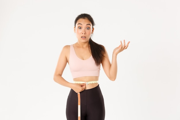 Fitness, healthy lifestyle and wellbeing concept. surprised asian girl on diet, sportswoman wrap measuring tape around waist and look impressed as lose weight with workout