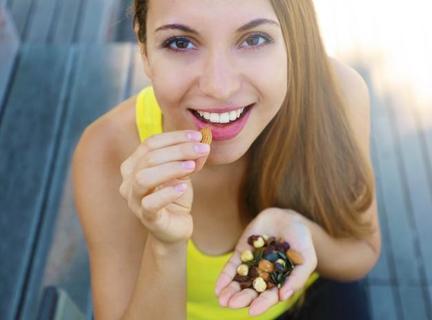 견과류 씨앗 말린 과일 야외 믹스를 먹는 피트니스 건강한 여자. 프리미엄 사진