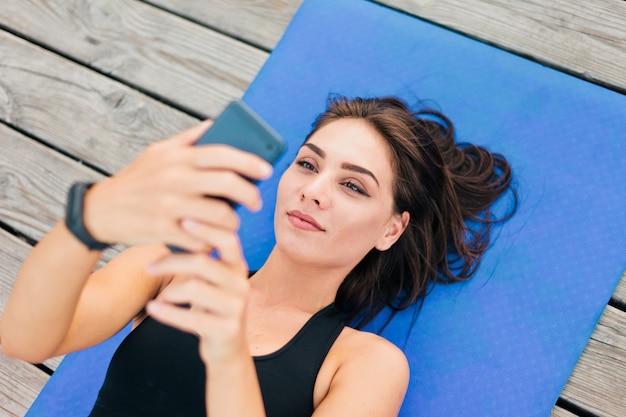 Здоровая женщина фитнеса в спортивной одежде лежит на циновке и держит смартфон в руках на деревянных досках.