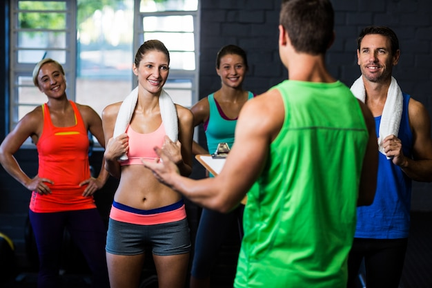 Fitness instructor discussing with happy people