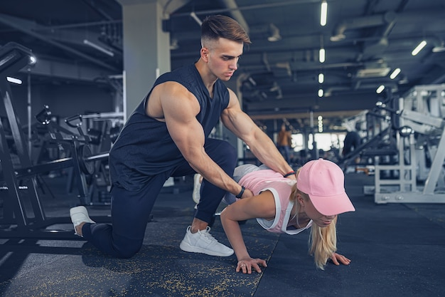 Fitness instructor help girl to do push ups on training in fitness center