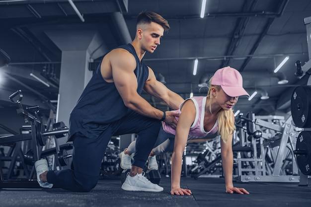 Фитнес-инструктор помогает девушке отжиматься на тренировке в фитнес-центре