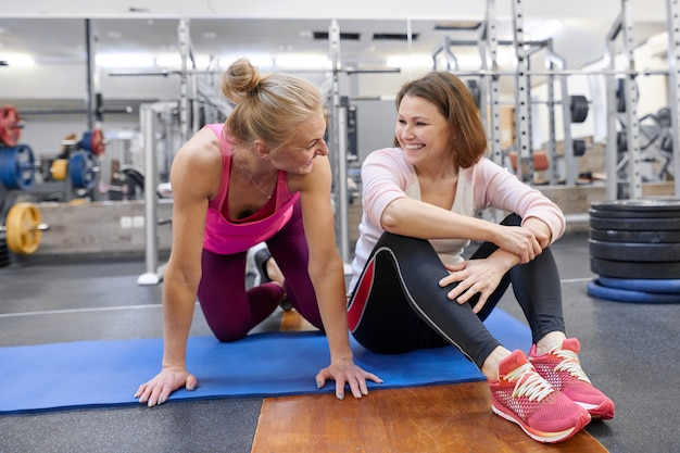 Fitness instructor and mature woman at gym.