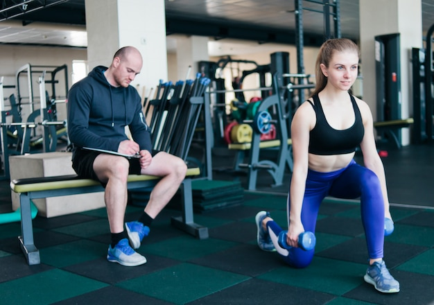 Фитнес-инструктор контролирует и записывает в тетради результаты тренировок молодой спортивной блондинки, выполняющей упражнения, выпады с гантелями в руках в спортзале