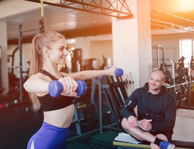 Фитнес-инструктор наблюдает и записывает в блокнот результаты тренировки молодой спортивной блондинки, выполняющей упражнения с гантелями в руках в тренажерном зале