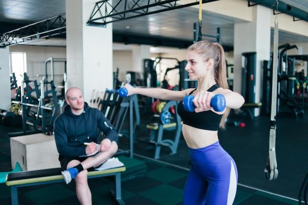 Фитнес-инструктор контролирует и записывает в тетради результаты тренировок молодой спортивной блондинки, выполняющей упражнения с гантелями в руках в тренажерном зале