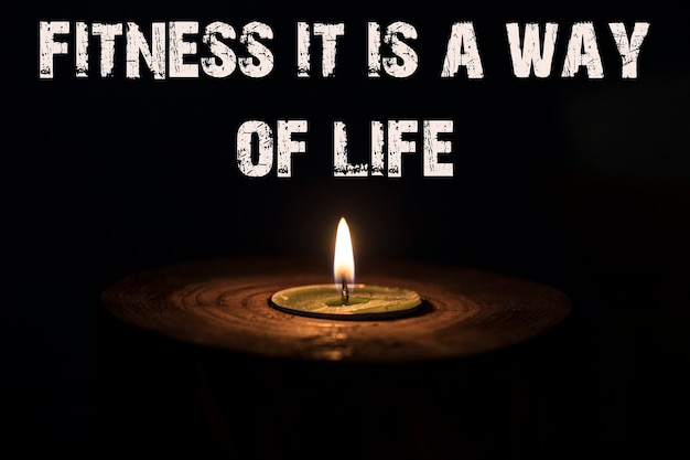 Fitness it is a way of life - white candle with dark background - in a wooden candlestick.