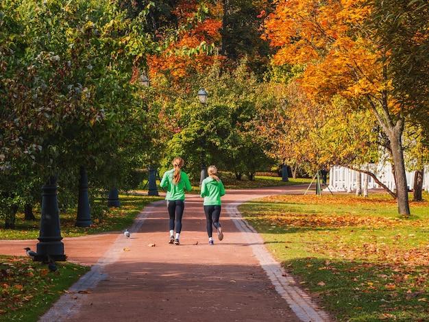 フィットネスジョギング。 2人の女の子が一緒に秋の公園でジョギングします。