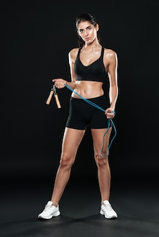 Fitness lady in gym standing over black wall and make sport exercises holding jumping rope