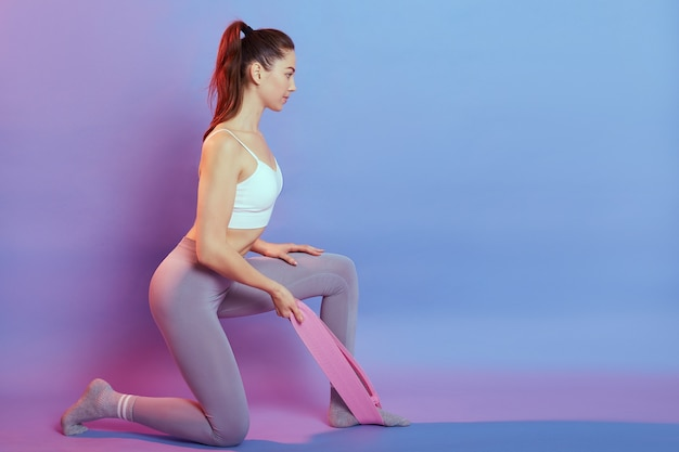 Fitness lady wearing top and leggins sitting on floor on one knee, using resistance band, looking ahead, woman has ponytail, looks concentrated, copy space for advertisement.