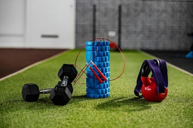 Фитнес-образ жизни и оборудование. спортивный инвентарь на искусственной зеленой траве в тренажерном зале - ролик, гантели, резинка, чайник. стены спортзала размыты, акцент на переднем плане