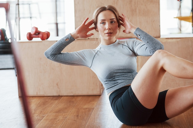 Fitness and lifestyle concept. sportive young woman does abs in the gym at morning time