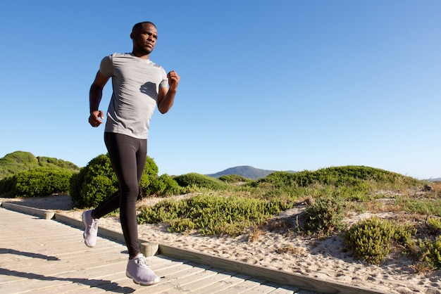 Fitness male model running at the beach