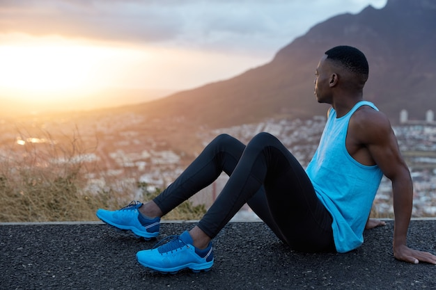 Il maschio fitness si siede di lato, ha la pelle nera, le mani muscolose, vestito con abbigliamento sportivo, guarda attentamente all'alba, posa sulle montagne, si prende una pausa dopo una corsa intensa. sport, natura