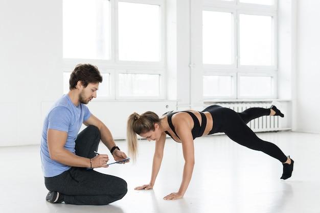 Мужчина и женщина фитнеса во время тренировки гимнастики с в тренажерном зале.