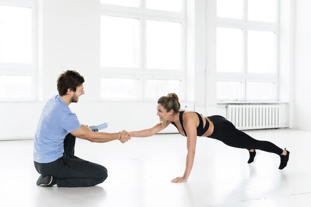 ジムでの体操トレーニング中のフィットネスの男性と女性。
