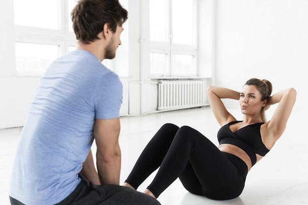 체육관에서 운동하는 동안 피트니스 남자와 여자. 복부 근육을위한 크런치 운동.
