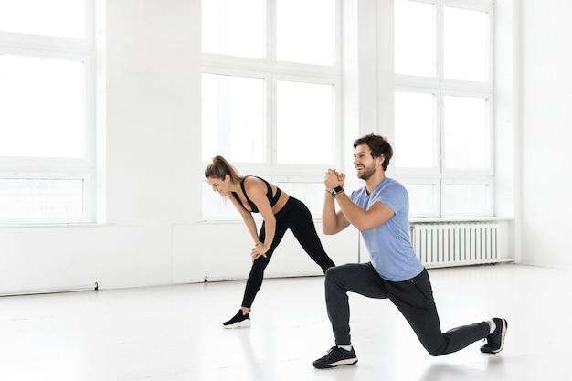 체육관에서 운동하는 동안 피트니스 남자와 여자. 둔근과 엉덩이 근육을위한 폐 운동.