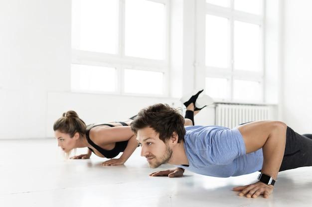 ジムでのトレーニング中のフィットネスの男性と女性。腕立て伏せは胸と上腕三頭筋を鍛えます。