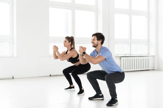 체육관에서 운동하는 동안 피트니스 남자와 여자. 스쿼트는 둔근과 엉덩이 근육을위한 운동입니다.