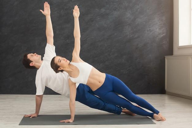 ジムでサイドプランクポーズでヨガをトレーニングするフィットネス、男性と女性。若いカップルは運動をし、スペースをコピーします