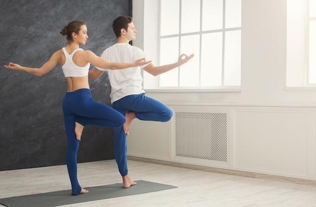 フィットネス、男性と女性が木のポーズでヨガをトレーニングします。若いカップルは、窓、背面図、コピースペースでリラックスした運動をします