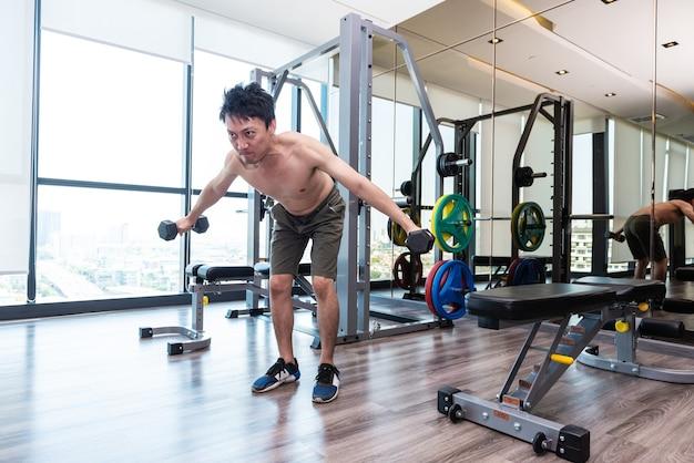 フィットネスマンはダンベルを持ち上げてトレーニングや運動をしています。スポーツジムのフィットネスルームで。