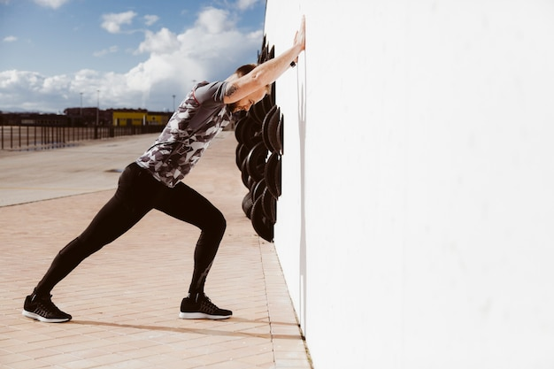 Fitness man doing push-ups against wall