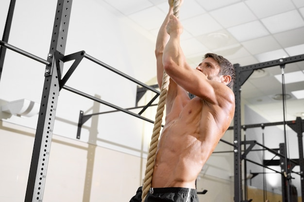 Fitness man doing rope climb exercise in gym